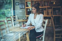 Working on document. Smiling business woman writing on document royalty free stock image