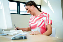 Smiling business woman writing in a notepad. Smiling business woman writing in her notepad on her desk Royalty Free Stock Photo