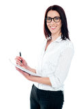 Smiling business woman writing on viral notedpad Royalty Free Stock Image