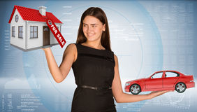 Smiling businesslady holding car and house Stock Photo