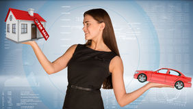 Smiling businesslady holding car and house Stock Image