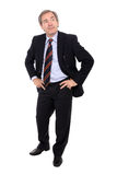 Smiling businessman. Closeup of smiling mature businessman with hands on hips, white studio background Royalty Free Stock Photography