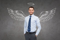 Smiling businessman with angel wings and nimbus. Business, angel investor, safety, security and people concept - smiling young businessman with wings and nimbus royalty free stock photography