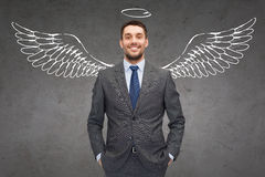 Smiling businessman with angel wings and nimbus Stock Images