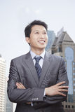 Smiling Businessman with arms crossed in front of Cityscape Stock Photo