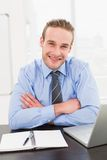 Smiling businessman with arms crossed at his desk Stock Photography