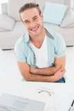 Smiling businessman with arms crossed at his desk Royalty Free Stock Images