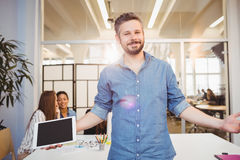 Smiling businessman with arms outstretched against coworkers Royalty Free Stock Image