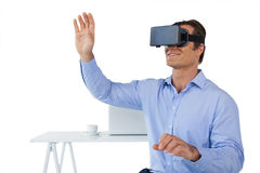 Smiling businessman with arms raised using vr glasses. While sitting against white background Royalty Free Stock Photography