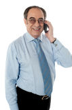 Smiling businessman attending phone call. Businessman communicating on mobile against white background Stock Photos