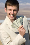 Smiling businessman with batch of dollars. Brunette smiling businessman holds fan of dollars royalty free stock images