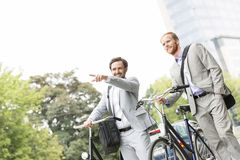 Smiling businessman with bicycle showing something to colleague on street Royalty Free Stock Image