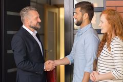 Students willing to rent apartment. Smiling businessman in black suit welcoming students willing to rent apartment Stock Photography