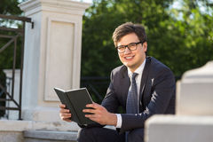 Smiling businessman with book Stock Images