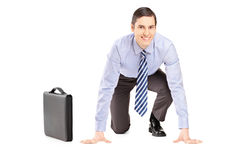 A smiling businessman with briefcase ready to run, looking at ca Stock Photos