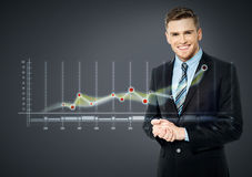 Smiling businessman and business strategy. Young business man standing with digital graph report Stock Photo
