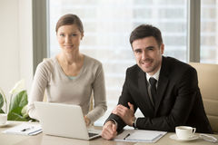 Smiling businessman and businesswoman looking at camera, busines. Smiling businessman and businesswoman looking at camera, confident successful boss and Royalty Free Stock Photography