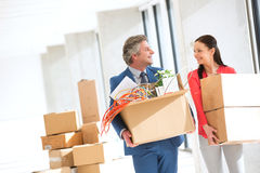 Smiling businessman and businesswoman looking at each other while carrying cardboard boxes in new office Royalty Free Stock Images