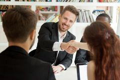 Smiling businessman and businesswoman shaking hands sitting at m. Eeting table, new partners greeting making first impression starting group negotiations Royalty Free Stock Photo