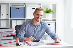 Smiling businessman calculates taxes. At desk in office Stock Image