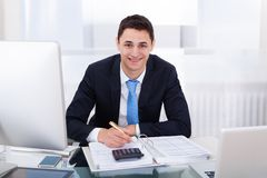 Smiling businessman calculating tax Royalty Free Stock Photos