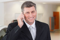 Smiling businessman calling with his mobile phone Stock Photos