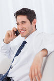 Smiling businessman calling with his mobile phone on sofa Stock Image