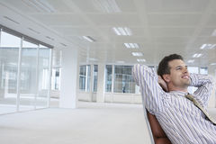 Smiling Businessman On Chair In New Office. Smiling young businessman relaxing on chair in empty office space stock photo