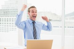 Smiling businessman cheering with arms up. In his office Stock Image
