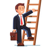 Smiling businessman climbing up the career ladder Royalty Free Stock Photography