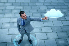 Smiling businessman with cloud projection outdoors Royalty Free Stock Image