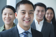 Smiling Businessman with co-workers in office portrait stock image