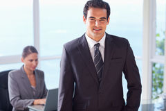 Smiling businessman with colleague behind him Stock Images