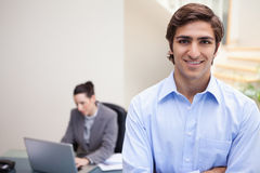 Smiling businessman with colleague on her laptop behind him Stock Photos