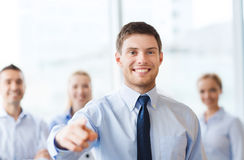 Smiling businessman with colleagues in office Stock Photos