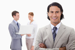 Smiling businessman with colleagues working on laptop behind him Stock Image