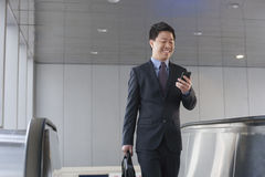 Smiling businessman coming up the escalator and looking down at his phone Stock Images