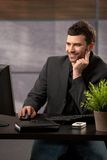 Smiling businessman with computer Stock Images