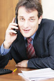 Smiling businessman at desk with phone Royalty Free Stock Photography