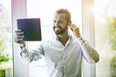 Businessman with digital tablet and earphones royalty free stock photo