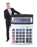 Smiling businessman displaying a calculator stock photos