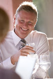 Smiling businessman drinking water on restaurant patio Royalty Free Stock Image