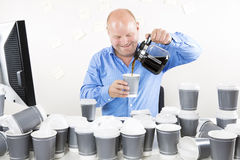 Smiling businessman drinks too much coffee Stock Photo