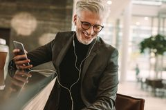 Smiling businessman in earphones and cellphone at cafe Royalty Free Stock Photography