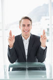Smiling businessman with fingers crossed at office desk Stock Images