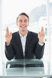 Smiling businessman with fingers crossed at office desk Stock Photography