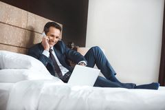 Smiling businessman in formal suit sitting on hotel room bed while using his laptop and talking royalty free stock image