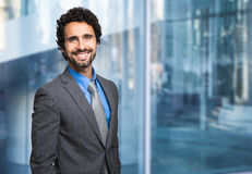 Smiling businessman in front of a glass wall Stock Images