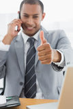 Smiling businessman gesturing thumbs up while on call Stock Image