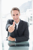 Smiling businessman gesturing thumbs up at office desk Royalty Free Stock Photos